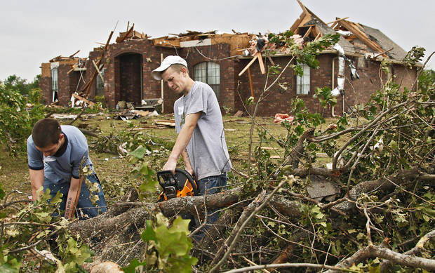 Little Axe students Miguel Varnell, left, and Ben Dodson  help clean up tornado debris Wednesday. Varnell and Dodson and their friend, Cody Brown, whose school was destroyed by a twister, volunteered their time to help in a neighborhood near SE 59 and Peebly Road. Photo by Chris Landsberger, The Oklahoman