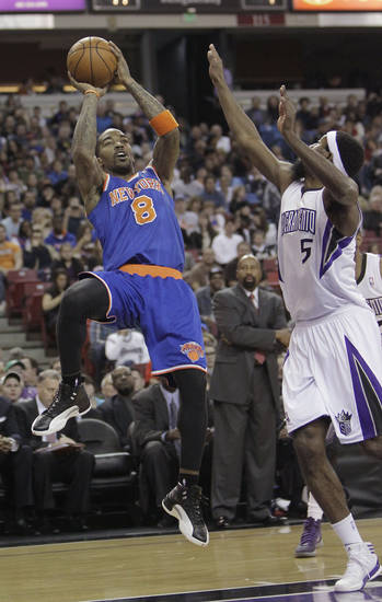 New York Knicks guard J.R. Smith, left, shoots over Sacramento Kings forward John Salmons during the first quarter of an NBA basketball game in Sacramento, Calif., Friday, Dec. 28, 2012.(AP Photo/Rich Pedroncelli)