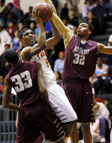 Stephen Clark (5) of Douglass shoots between Omarkio Collins (33) and Deshawn Watson (32) of Northeast during a boys high school basketball game between Douglass and Northeast at Douglass High School in Oklahoma City, Friday, Feb. 8, 2013. Photo by Nate Billings, The Oklahoman