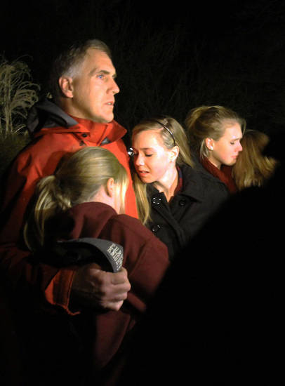 A man hugs his young daughters as they attend a vigil at Saint Rose of Lima church at Saint Rose of Lima church, Friday, Dec. 14, 2012 in Newtown, Conn. A man killed his mother at home and then opened fire Friday inside the elementary school where she taught, massacring 26 people, including 20 children, as youngsters cowered in fear to the sound of gunshots echoing through the building and screams coming over the intercom. (AP Photo/The Journal News, Frank Becerra Jr.)  NYC OUT, NO SALES, ONLINE OUT, TV OUT, NEWSDAY INTERNET OUT; MAGS OUT