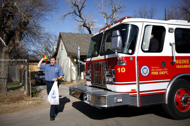 Lt. Keith Castillo hands out toys in the Westlawn Gardens neighborhood in Oklahoma City, Saturday, Dec. 24, 2011. Photo by Sarah Phipps, The Oklahoman
