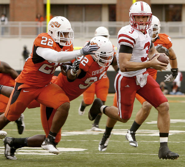 Nebraska's Taylor Martinez runs past OSU's James Thomas, left, and Darius Hart during the college football game between the Oklahoma State Cowboys (OSU) and the Nebraska Huskers (NU) at Boone Pickens Stadium in Stillwater, Okla., Saturday, Oct. 23, 2010. Photo by Bryan Terry, The Oklahoman