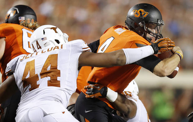 Oklahoma State&#039;s J.W. Walsh (4) tries to escape from Texas&#039; Jackson Jeffcoat (44) during a college football game between Oklahoma State University (OSU) and the University of Texas (UT) at Boone Pickens Stadium in Stillwater, Okla., Saturday, Sept. 29, 2012. Oklahoma State lost 41-36. Photo by Bryan Terry, The Oklahoman