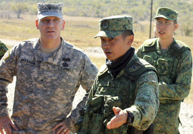Staff Sgt. Jeffrey Yap, a Singaporean Armed Forces crew chief, explains Tuesday to Brig. Gen. Brian McKiernan, U.S. Army chief of field artillery, details of an  infantry carrier. Photos by Keith Pannell, Fort Sill
