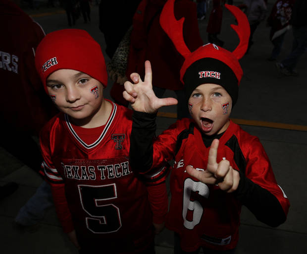 "Texas Tech fans Landon Banks, 8, wears a ""crab tree"" hat and flashes raider pistols as friend Jacob Herrell, also 8, looks on before the college football game between the University of Oklahoma Sooners and Texas Tech University at the Gaylord Family -- Oklahoma Memorial Stadium on Saturday, Nov. 22, 2008, in Norman, Okla.   The tech fans are from Maypearl, Texas.  BY STEVE SISNEY, THE OKLAHOMAN"
