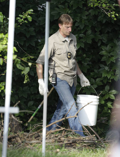 An investigator carries out a bucket  Sunday, July 21, 2013 near where three bodies were found in East Cleveland, Ohio. Searchers rummaging through vacant houses in a neighborhood where three female bodies were found wrapped in plastic bags should be prepared to find one or two more victims, a police chief said Sunday. (AP Photo/Tony Dejak)