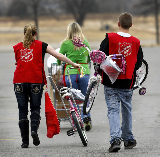 Two volunteers follow a client to her car where they will load toys and bicycles. The Salvation Army and Feed The Children teamed to distribute bicycles and toys and handed out boxes of food at their annual distribution event Wednesday.   Photo by Jim Beckel, The Oklahoman <strong>Jim Beckel - THE OKLAHOMAN</strong>