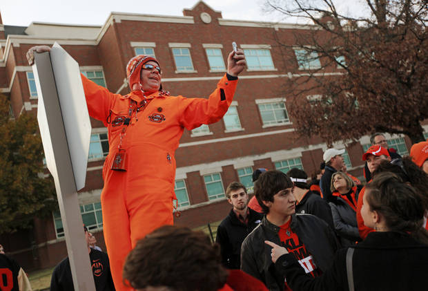 "Lee Redick, ""Mr. Orange Power"", of Sapulpa, Okla., takes video of the crowd at the Spirit Walk before the Bedlam college football game between the Oklahoma State University Cowboys (OSU) and the University of Oklahoma Sooners (OU) at Boone Pickens Stadium in Stillwater, Okla., Saturday, Dec. 3, 2011. Photo by Nate Billings, The Oklahoman"