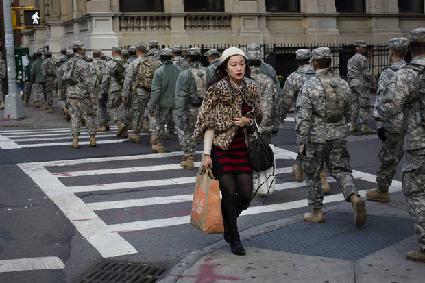 A woman with her groceries passes a group of National Guardsmen as they march up 1st Avenue towards the 69th Regiment Armory, Saturday, Nov. 3, 2012, in New York. National Guardsmen remain in Manhattan as the city begins to move towards normalcy following Superstorm Sandy earlier in the week. (AP Photo/ John Minchillo) ORG XMIT: NYJM105