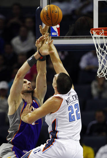 Charlotte Bobcats' Byron Mullens, right, blocks a shot by Phoenix Suns' Marcin Gortat, left, during the first half of an NBA basketball game in Charlotte, N.C., Wednesday, Nov. 7, 2012. (AP Photo/Chuck Burton)