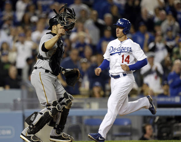 Pittsburgh Pirates catcher Russell Martin watches the infield as Los Angeles Dodgers' Mark Ellis scores on a Matt Kemp double in the sixth inning of a baseball game in Los Angeles Friday, April 5, 2013. (AP Photo/Reed Saxon)