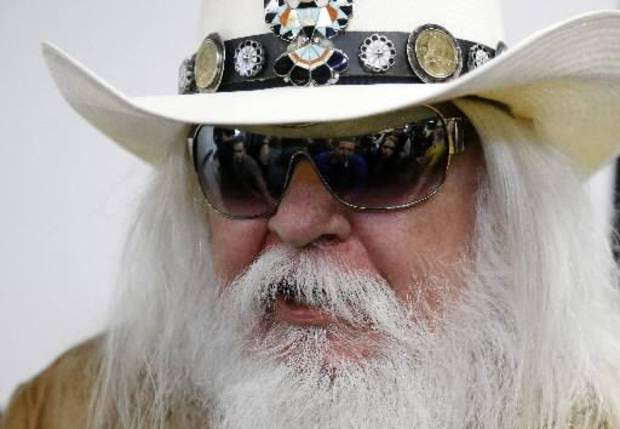 Reporters are reflected in the sunglasses of Leon Russell as he answers a question at a news conference in Tulsa, Okla., Tuesday, Jan. 29, 2013. The Oklahoma Historical Society has acquired a large collection of works by the legendary musician and native Oklahoman that are intended for display in a planned pop culture museum in Tulsa. (AP Photo)