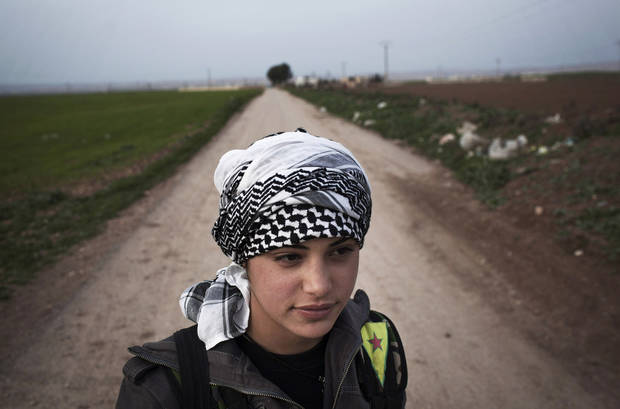 A Kurdish female member of the Popular Protection Units stands guard at a check point near the northeastern city of Qamishli, Syria, Sunday, March 3, 2013. (AP Photo/Manu Brabo)