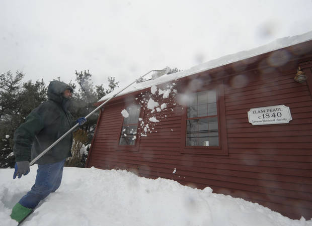 Al Brewer uses a snow rake to clear snow off the roof of his home that dates back to 1840,  as rain falls on Monday, Feb. 11, 2013,  in Vernon, Conn.  (AP Photo /Journal Inquirer, Jim Michaud)