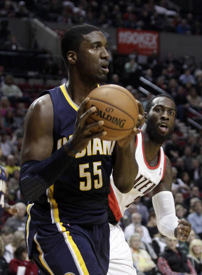 Indiana Pacers center Roy Hibbert, left, looks for an outlet to pass as Portland Trail Blazers center J.J. Hickson defends during the first quarter of an NBA basketball game in Portland, Ore., Wednesday, Jan. 23, 2013. (AP Photo/Don Ryan)