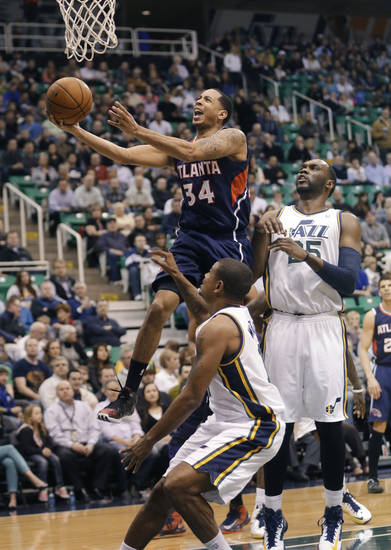 Atlanta Hawks' Devin Harris (34) goes to the basket as Utah Jazz's Earl Watson (11) and Al Jefferson (25) watch during the first quarter of an NBA basketball game Wednesday, Feb. 27, 2013, in Salt Lake City. (AP Photo/Rick Bowmer)