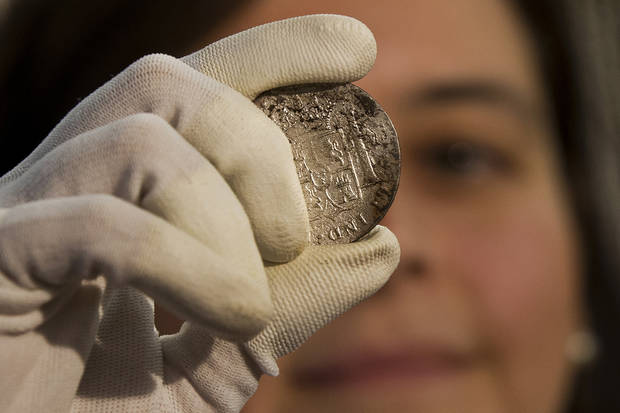 A worker of the ministry holds up for photographers a silver coin from the shipwreck of a 1804 galleon, on its first display to the media at a ministry building, in Madrid, Friday, Nov. 30, 2012. Spanish cultural officials have allowed the first peep at 16 tons (14.5 metric tons) of the shipwreck, &#039;Nuestra Senora de las Mercedes&#039; a treasure worth an estimated $500 million that a U.S. salvage company gave up after a five-year international ownership dispute. (AP Photo/Daniel Ochoa de Olza)