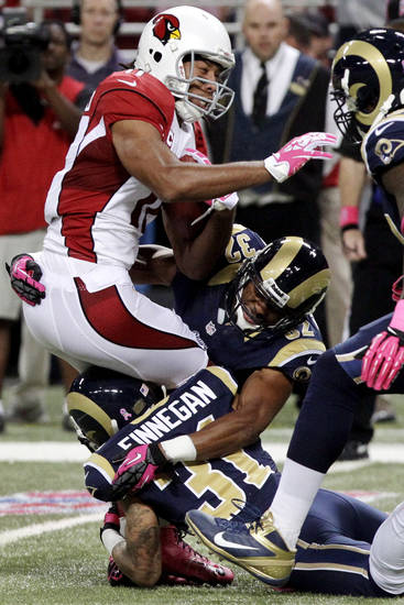Arizona Cardinals wide receiver Larry Fitzgerald is stopped by St. Louis Rams cornerbacks Cortland Finnegan (31) and Bradley Fletcher (32) after catching a pass during the first quarter of an NFL football game, Thursday, Oct. 4, 2012, in St. Louis. (AP Photo/Seth Perlman)