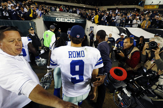 Dallas Cowboys quarterback Tony Romo is escorted off the field after an NFL football game against the Philadelphia Eagles, Sunday, Nov. 11, 2012, in Philadelphia. Dallas won 38-23. (AP Photo/Julio Cortez)