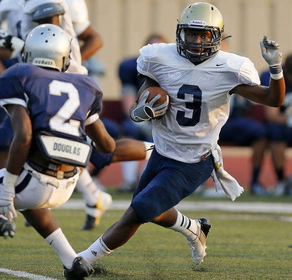 Southmoore's Jaelon Walker (3) carries the ball against Enid's Alex Lofton (2) during a high school football scrimmage at Moore Stadium in Moore, Okla., Friday, Aug. 17, 2012. Photo by Nate Billings, The Oklahoman