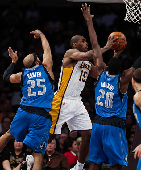 Los Angeles Lakers forward Metta World Peace, middle, attempts a shot over Mavericks center Ian Mahinmi, right, and guard Vince Carter, left, during the first half of an NBA basketball game, Sunday, April 15, 2012, in Los Angeles. (AP Photo/Bret Hartman)