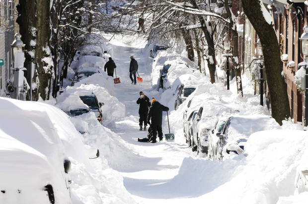 People pause for a picture while digging out their cars in Boston, Sunday, Feb. 10, 2013. A howling storm across the Northeast left the New York-to-Boston corridor shrouded in 1 to 3 feet of snow Saturday, stranding motorists on highways overnight and piling up drifts so high that some homeowners couldn&#039;t get their doors open. More than 650,000 homes and businesses were left without electricity.(AP Photo/Winslow Townson)