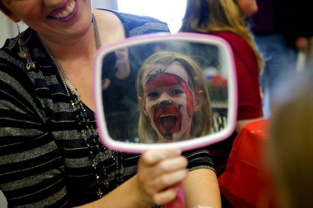 Daniella Shobert, 4, laughs as she see her painted face at a birthday party for Clifford the Big Red Dog in Moore, Okla., Saturday, Feb. 16, 2013. Photo by Bryan Terry, The Oklahoman