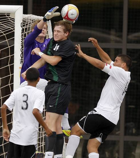 Norman North's Jackson Biles, left, and Curtis McCrae go for the ball between Tulsa Union's Ivan Evangelista, left, and Cristian Mata during the boys 6A state championship soccer game in Newcastle, Okla., Saturday, May 12, 2012. Photo by Bryan Terry, The Oklahoman