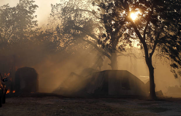 Smoke is filtered through the sun as homes burn in Luther, Okla.,  during a large wildfire Friday, Aug. 3, 2012. Photo by Sarah Phipps, The Oklahoman