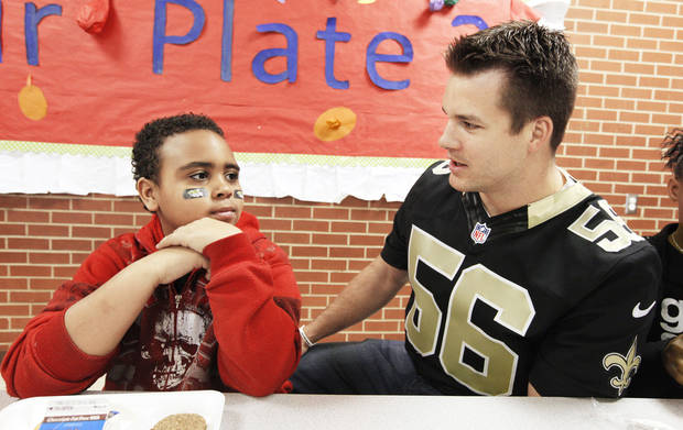 Bethany native New Orleans Saints linebacker Chris Chamberlain, right, visits with third-grader Jaren Smith, 9, during a National School Breakfast Week event at Pleasant Hill.