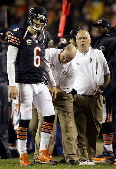Trainers look at Chicago Bears quarterback Jay Cutler (6) after Cutler took a late hit by Houston Texans linebacker Tim Dobbins in the first half of an NFL football game in Chicago, Sunday, Nov. 11, 2012. The Texans won 13-6. Dobbins was called for an unnecessary roughness penalty on the play. Cutler did not return in the second half after suffering a concussion. (AP Photo/Nam Y. Huh)