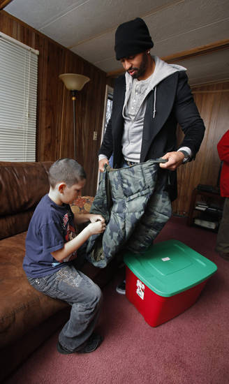 CHILD / CHILDREN / KIDS / CHRISTMAS / HOLIDAY / GIFTS: Baseball superstar Matt Kemp helps Corey Patzkie, 9, with his new coat as he delivers presents to a trailer community on Thursday, Dec. 22, 2011, in Midwest City, Okla.   Photo by Steve Sisney, The Oklahoman