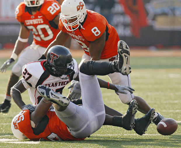 Texas Tech's Edward Britton (27) fumbles the ball after getting hit by Oklahoma State's Kellen Tillman (56) during the second half of the college football game between the Oklahoma State University Cowboys (OSU) and the Texas Tech University Red Raiders (TTU) at Boone Pickens Stadium in Stilllwater, Okla., on Saturday, Sept. 22, 2007. OSU won, 49-45. By NATE BILLINGS, The Oklahoman