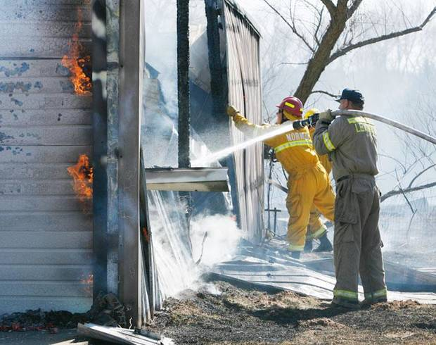 THIRD PLACE, FEBRUARY: Firefighters work to extinguish flames in a barn that was set ablaze by a grass fire near SE 108th and Maguire Road in Slaughterville, Oklahoma, on Friday February 20, 2009. Photo by Steve Sisney, The Oklahoman