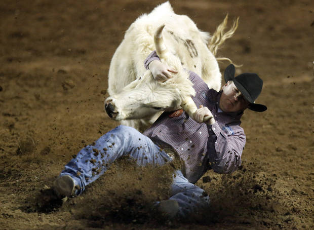 Stewart Gulager of Garland, Kans., wrestles a steer during the steer wrestling event at the International Finals Rodeo at the State Fair Arena in Oklahoma City,  Saturday,Jan. 19, 2013. Photo by Sarah Phipps, The Oklahoman