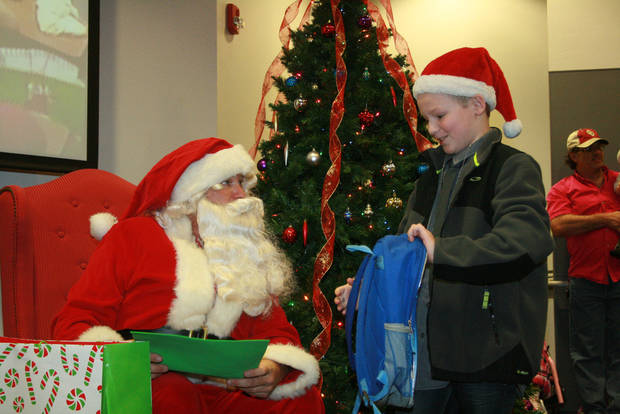 Bradley Sprinkle, 10, turns the table on Santa Claus by bringing him a present Sunday at the J.D. McCarty Center�s annual Christmas party for children. PHOTO BY LYNETTE LOBBAN, FOR THE OKLAHOMAN