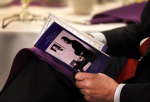 "A breakfast guest reads the souvenir program during the 16th annual Midwest City Dr. Martin Luther King, Jr. Prayer Breakfast inside the Reed Conference Center Monday morning, Jan. 21, 2013. The theme of this year's event is ""The Wisdom of Peace."" About 400 people attended.   Photo by Jim Beckel, The Oklahoman"