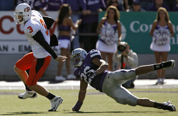 Oklahoma State's Brandon Weeden (3) runs with the ball past Kansas State's Jarell Childs (26) during the second half of the college football game between the Oklahoma State University Cowboys (OSU) and the Kansas State University Wildcats (KSU) on Saturday, Oct. 30, 2010, in Manhattan, Kan.   Photo by Chris Landsberger, The Oklahoman