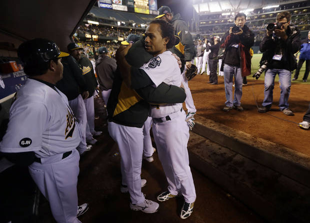 Oakland Athletics manager Bob Melvin hugs Coco Crisp, right, after the A's lost 6-0 to the Detroit Tigers in Game 5 of an American League division baseball series in Oakland, Calif., Thursday, Oct. 11, 2012. (AP Photo/Marcio Jose Sanchez)