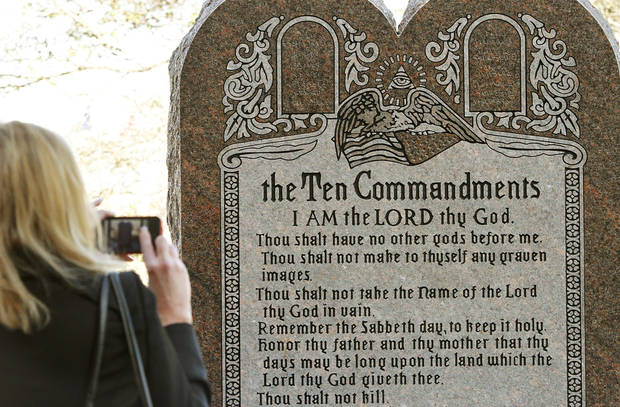 A woman takes a picture of this six-foot tall granite monument of the Ten Commandments after it was erected on the north side of the state Capitol grounds Thursday morning, Nov. 15, 2012.  Photo by Jim Beckel, The Oklahoman