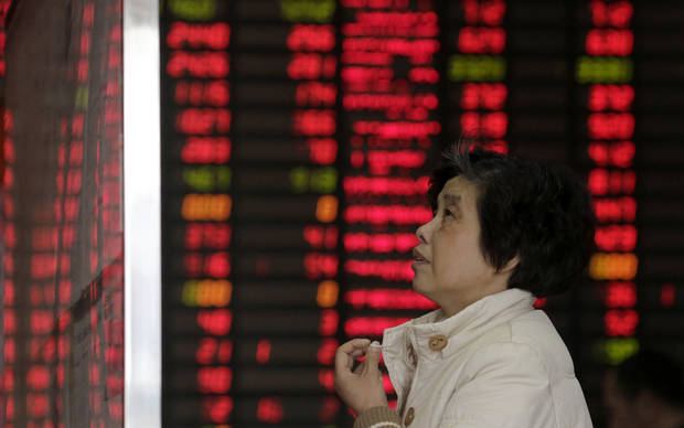 An investor looks at the stock bulletin board at a private securities company on Wednesday, March 6, 2013. The Dow's new all-time high and better economic data from the United States propelled Asian stock markets higher Wednesday. (AP Photo/Eugene Hoshiko)
