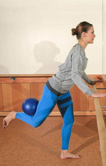 Model Emoly demonstrates Standing Seat Work, a Barre3 posture. Come forearms distance from the barre (or waist high surface), soften your knees and hinge forward at the waist bringing your hands wide. Bend your leg and externally rotate your knee until you feel your outer seat catch keeping both hips facing forward. Targets the outer seat. Photo by Chris Landsberger. <strong>CHRIS LANDSBERGER</strong>