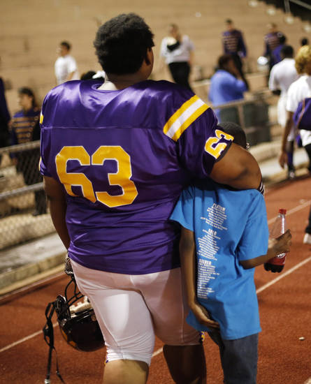 NWC's Darius Bias leaves the field with his arm around a young man at the Northwest Classen vs. Western Heights high school football game at Taft Stadium Thursday, September 20, 2012. Photo by Doug Hoke, The Oklahoman