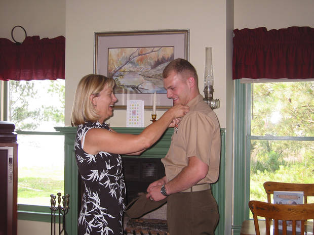   This May 2004 photo provided by Lisa Freeman shows her pinning on her son Matthew&#039;s 1st Lt. rank after his father swore him at their home in Richmond Hill, Ga. Marine Capt. Matthew C. Freeman was killed by a sniper&#039;s bullet on Aug. 7, 2009, northeast of Kabul, Afghanistan. Lisa Freeman says, &quot;I walk around this country and look in faces that don&#039;t even know we&#039;re at war anymore. People that are going about their everyday lives, not realizing that they&#039;ve been kept safe by this amazing group of young men and women who have been willing to sacrifice so much.&quot; (AP Photo/Lisa Freeman)  