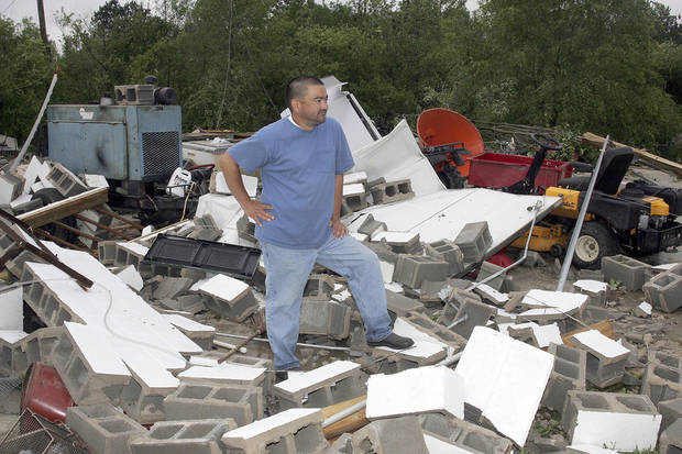 "Jimmy King looks at what is left of his three bay garage shop after a storm hit at his Arab, Ala.  home on Wednesday,  April 27, 2011.  A wave of thunderstorms with near hurricane-force winds pushed across Alabama on Wednesday, killing at least five people including a woman in a mobile home and sending snapped tree limbs onto cars and homes. The widespread destruction caused Gov. Robert Bentley to declare a state of emergency by midday, saying tornadoes, severe thunderstorms, hail, and straight-line winds caused damage to ""numerous homes and businesses"" in Alabama.   (AP Photo/The Huntsville Times, Robin Conn)"