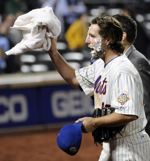 New York Mets pitcher R.A. Dickey waves to the fans as he leaves the field after getting a cream pie for pitching a one-hitter as the Mets defeated the Baltimore Orioles, 5-0, in an interleague baseball game, Monday, June 18, 2012, at Citi Field in New York. (AP Photo/Bill Kostroun) ORG XMIT: NYM119
