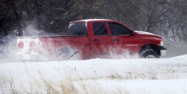A 4 wheel drive vehicle drives through deep snow on S. Lakewood Drive in Logan County, Oklahoma February  1, 2011. Photo by Steve Gooch, The Oklahoman