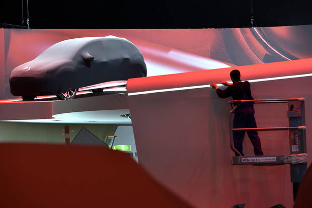 A worker is busy at the Citroen booth next to a car during last preparations prior to the opening of the press preview days at the 83nd Geneva International Motor Show in Geneva, Switzerland, Saturday, March 2, 2013. The Motor Show will open its gates to the public from March 7 to 17, presenting more than 260 exhibitors and more than 130 world and European premieres. (AP Photo/Keystone, Martial Trezzini)