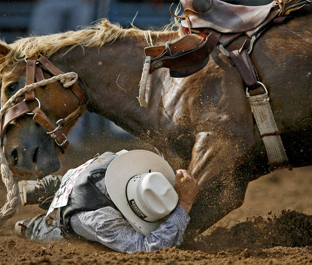 Tyke Kipp of Lordsburg, N.M., takes cover after falling off his horse in the saddle bronc event during the International Finals Youth Rodeo in Shawnee, Okla., Friday, July 16, 2010.  Photo by Bryan Terry, The Oklahoman