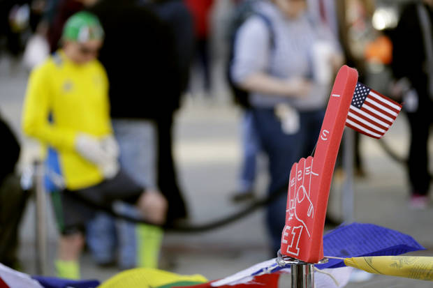 A foam finger, right, stands at a makeshift memorial on Boylston Street near the blast site of the Boston Marathon explosions, as a man wearing running gear stops to pay respects, Thursday, April 18, 2013, in Boston. The city continues to cope following Monday's explosions near the finish line of the marathon. (AP Photo/Julio Cortez)